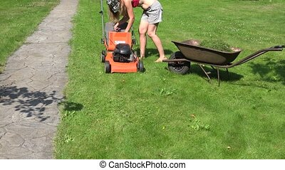 Female farmer start lawn mower and cut grass. 4K - Female...