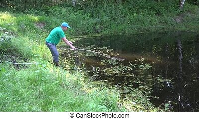 man clean with rake grass and creeper rural pond summertime....