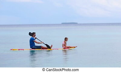 Little girl and young dad on surfboard
