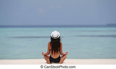Happy relaxed young woman practicing yoga outdoors at white beach