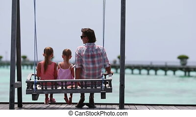 Adorable little girls and young father on swing