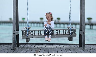 Adorable little girl having fun during beach vacation