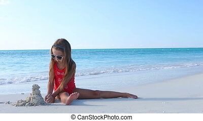 Little girl making sand castle and playing at tropical beach