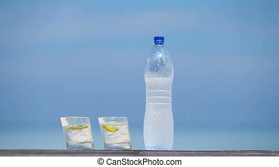 Glasses of waters with lemon and bottle on wooden on sea background