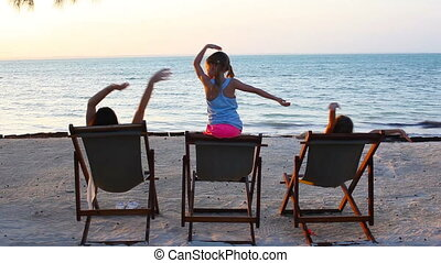 Little girls and mother sitting on beach chairs at sunset