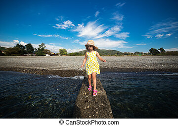 Cute little girl in yellow dress and straw hat walking on...