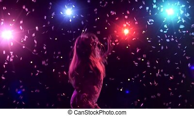 Silhouette of dancing girl with disco style lights and...