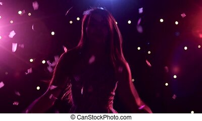 Silhouette of dancing girl with disco style lights and confetti
