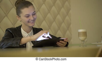 Cheerful girl using a tablet, smiling in cafe. 4K.