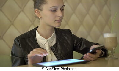 Girl sitting in cafe, using a tablet, speaking on the phone,...
