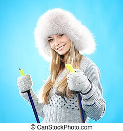 Girl in winter clothes with ski poles. Happy skier