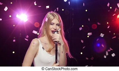 Blonde girl singing into a retro microphone strobe lighting...