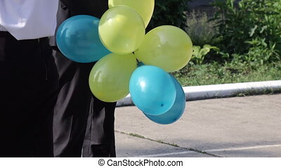 Gel balls in hand boy - Yellow and blue balloons in hand
