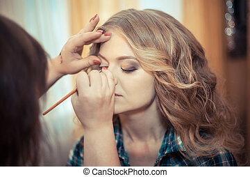 make-up artist doing professional make up of young woman