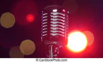 Retro shiny microphone rotating against blurry flashing lights. Close-up