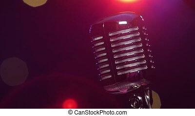 Vintage shiny microphone reflects glitter confetti against blurry flashing lighting