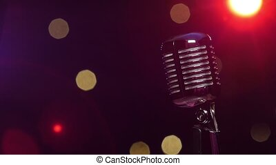 Vintage microphone against dark blurry background with...