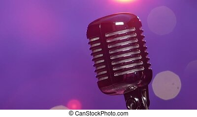 Retro microphone against blurry purple stage lighting with...
