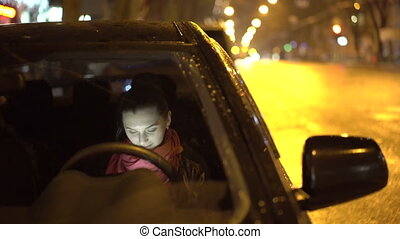 View og girl using the tablet through car window at night....