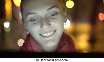 Happy face of the girl smiling and looking on the tablet at night. 4K