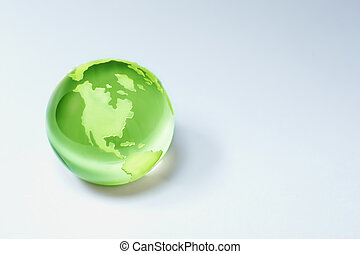 green world - glass globe on grey background, toned and...