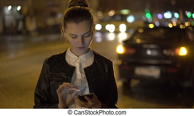 Young girl standing at the night road, using phone. 4K.