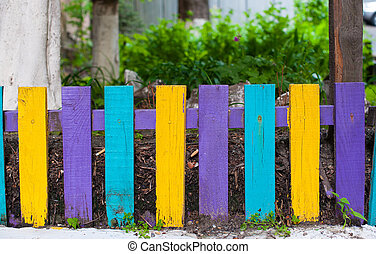 Decorative multicolored wooden fence near the house