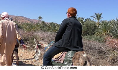 Young man riding donkey in Morocco - Young man in his...