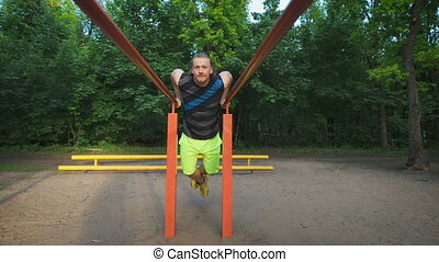 Muscular man during his workout in park. Dips, exercise...