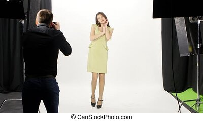 Girl and photographer in studio. Man holds the photography. White