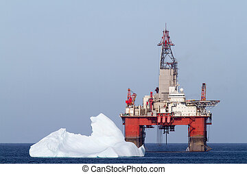 Oil and Gas - Iceberg next to a offshore oil drilling...