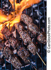 beef skewers grilling on flames from charcoal bbq, top view...