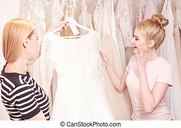 Talented designer showing bridal gown to customer - Skillful...