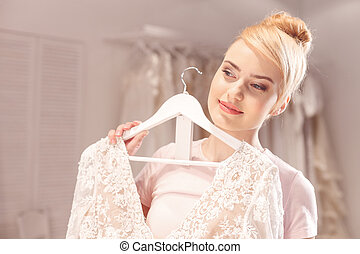 Cute future bride is choosing perfect attire - Portrait of...