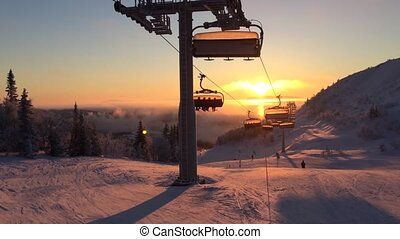cableway in the rays of the setting sun among snow-capped...