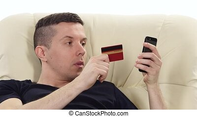 Online shopping on the sofa Credit card and phone White...