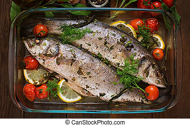 Two baked seabass in a baking dish with spices on an wooden...