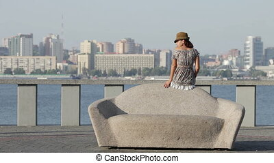 Beautiful girl sits on a lithoidal sofa. - A beautiful girl...