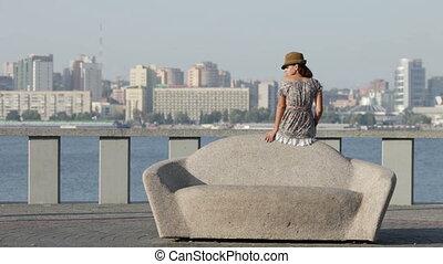 Beautiful girl sits on a lithoidal sofa. - A beautiful girl...