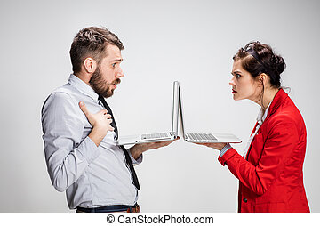 The young businessman and businesswoman with laptops...