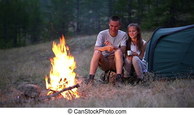 Couple at the camping with campfire in summer