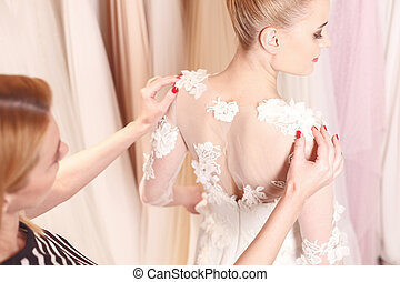 Skillful female tailor is fitting bridal clothing - Pretty...