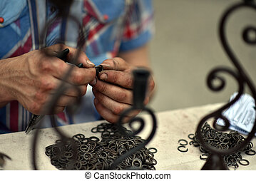 Master blacksmith engaged in assembling of chainmail rings -...