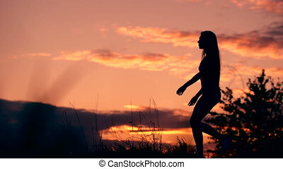 Silhouette of the woman standing lonely at the field during beautiful sunset