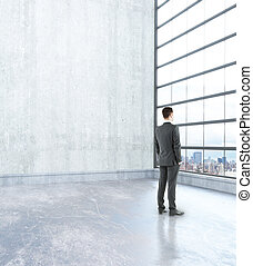 Man in room - Thoughtful businessman in concrete interior...