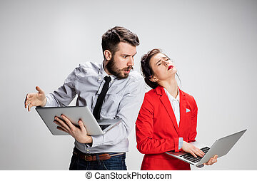 The young businessman and businesswoman with laptops on gray...