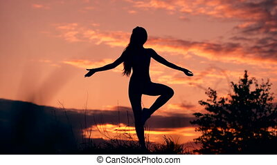 In harmony with oneself and the world. Silhouette of woman standing at yoga pose during an amazing sunset.