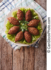 Arabic cuisine: meat appetizer kibbeh close-up on a plate...
