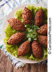 Arabic beef meatballs kibbeh close-up on a plate vertical...