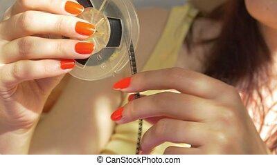 Woman Rolling a Reel - Woman is rolling a 8mm film reel